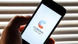 Auf dem Bildschirm eines Smartphones ist der Startschirm einer Corona Warn-App abgebildet
