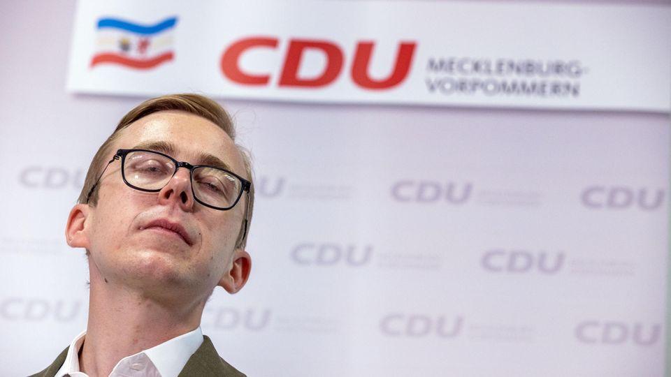 Philipp Amthor vor dem Logo der CDU Mecklenburg-Vorpommern