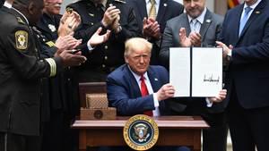 Donald Trump zeigt das unterzeichnete Gesetz im Rosengarten des Weißen Hauses