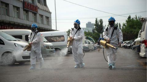Morgenlage: In Schutzausrüstung säubern und desinfizieren drei Männer eine Straße in Peking