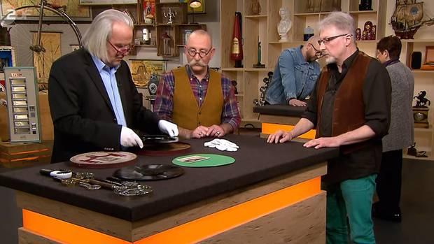 """""""Bares für Rares""""-Experte Albert Maier nimmt eine alte Schellackplatte in Augenschein. Moderator Horst Lichter und Verkäufer Horst Henry Schmitt hören seinen Ausführungen zu."""