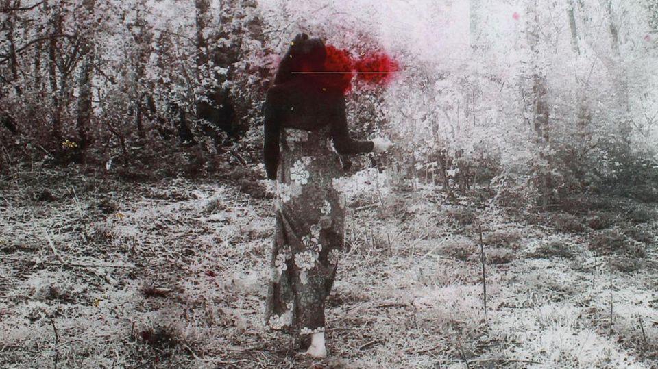 Eine verschwommene Aufnahme einer Frau im Wald