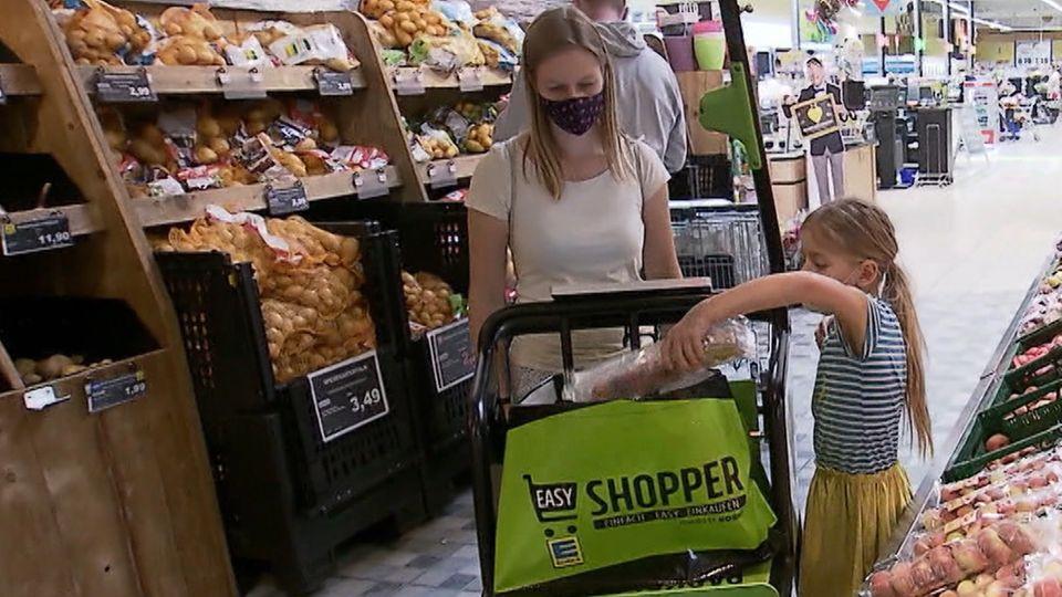 """Peggy Hoppe und ihre Tochter testen den neuen Einkaufswagen """"Easy Shopper"""" bei einer Edeka-Filiale."""