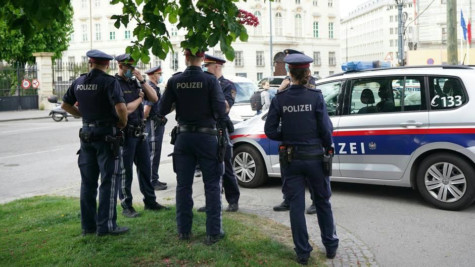 Polizisten stehen vor einem Polizeiwagen