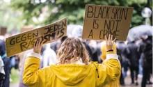 """""""Gegen jeden Rassismus"""" und """"·Black skin is not a crime"""" steht auf Schildern einer Demonstrantin in Stuttgart"""