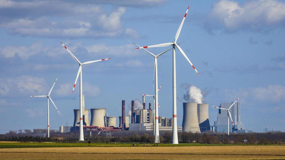 Selbst vor dem riesigen Braunkohlekraftwerk Neurath im Rheinland drehen sich inzwischen Windräder