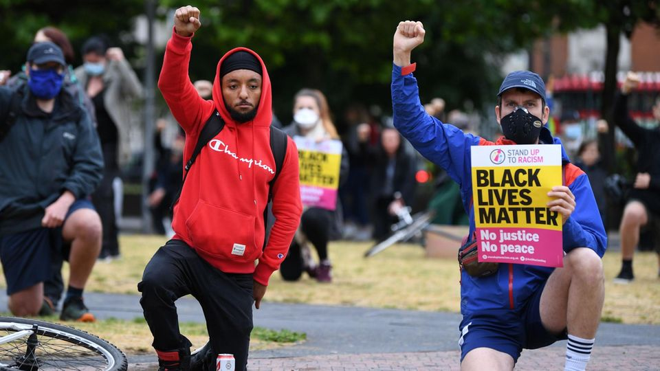 """Ein weißer und ein schwarzer Mann knien bei """"Black Lives Matter""""-Protesten"""