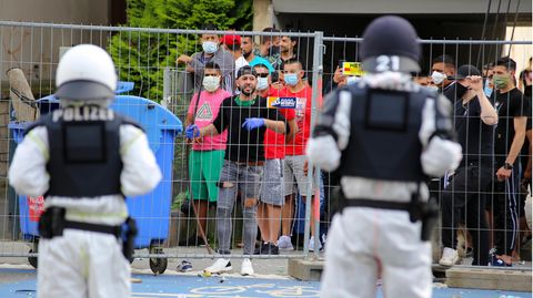 Polizisten sehen sich vor dem unter Quarantäne stehenden Wohnkomplex in Göttingen einer Gruppe junger Männer gegenüber