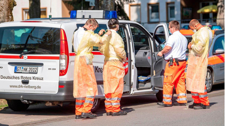 Helfer des Roten Kreuzes ziehen sich Mund-Nasenschutz und Schutzkleidung an und bereiten sich auf einen Einsatz vor