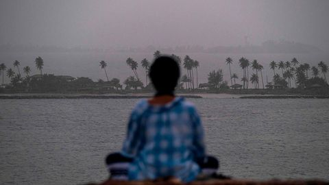 Eine Frau meditiert vor dem Panoramader Stadt San Juan, die von einerriesigen Wolke aus Saharastaub verhüllt ist