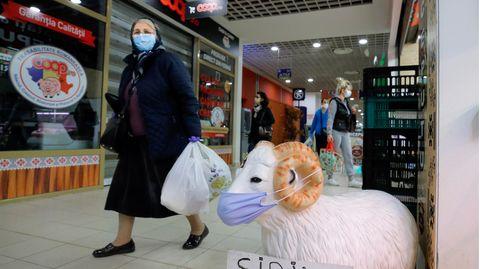 Eine ältere Frau mit Mundschutz geht in Rumäniens Hauptstadt Bucharest an einem Käse- und Fleischgeschäft vorbei