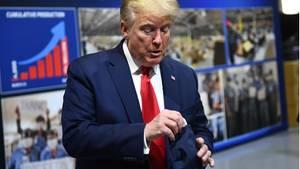 Donald Trump hantiert mit einer eingepackten Maske