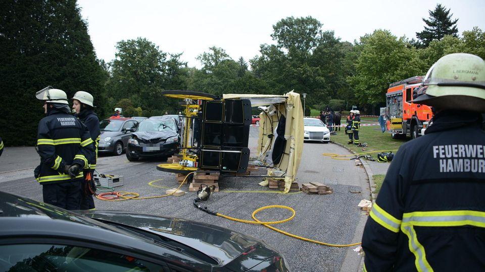 Einsatzkräfte der Feuerwehr sichern nach einem Unfall mit einer Pferdekutsche auf dem Friedhof Ohlsdorf den Unfallort