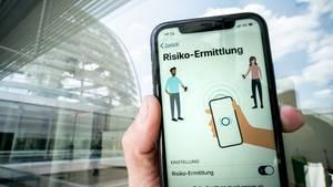 Die Corona-Warn-App mit der Seite zur Risiko-Ermittlung ist im Display eines Smartphone vor der Kuppel des Reichstags zu sehen