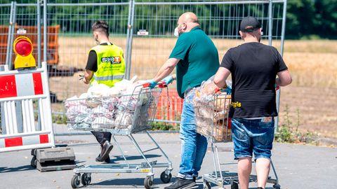Tönnies: Zwei Mitarbeiter eines Lebensmittelmarktes schieben in zwei Einkaufswagen Brot in die abgesperrte Siedlung