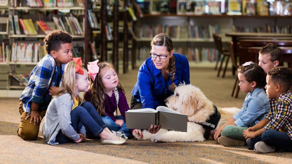 Kinder, eine Lehrerin und ein Hund sitzen um ein Buch