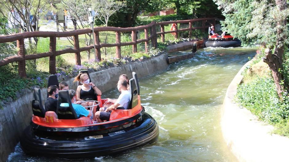 """Ein """"Mountain Rafting""""-Boot schwimmt durch den Kanal. Die Insassen tragen Mund-Nasen-Schutzmasken."""