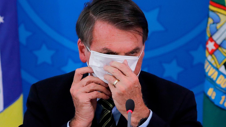 Bolsonaro versucht eine Maske aufzusetzen