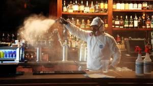 USA, St. Petersburg: Miteigentümer einer Desinfektionsfirma desinfiziert den Tresen in einem Gasthaus.Die Corona-Krise in den USA verschärft sich erneut dramatisch.