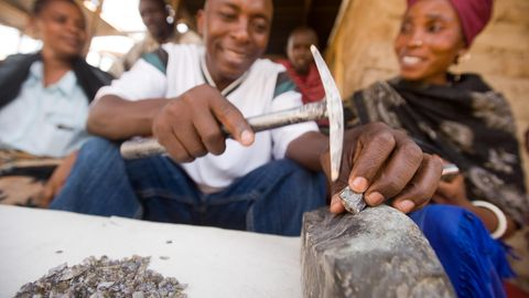 Ein Edelsteinhändler zerlegt auf einem Markt in Tansania einen Tansanit-Stein