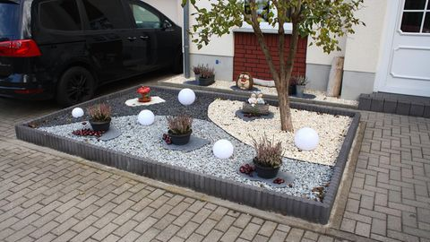 Mit Kieselsteinen und Lampen gestalteter Schottergarten vor einem Wohnhaus