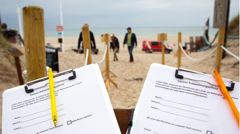"""Fragebögen zur Selbstauskunft zur Corona-Aufzeichnungspflicht sind am Eingang zum Bistro am Strandabschnitt """"Buhne 16""""bei Kampen auf Sylt"""