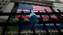 Ein Mundschutz hängt an einem Zaun vor der New Yorker Börse