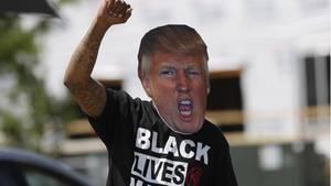 Demonstrant mit Trump-Maske ballt die rechte Faust