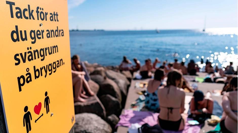 Ein Schild weist an einer vollen Badestelle in Malmö darauf hin, Abstand zu halten