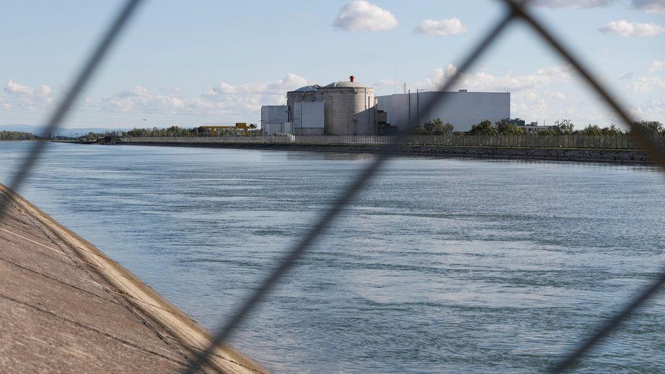 Blick durch ein Sicherheitszaun auf das Atomkraftwerk Fessenheim in Ostfrankreich