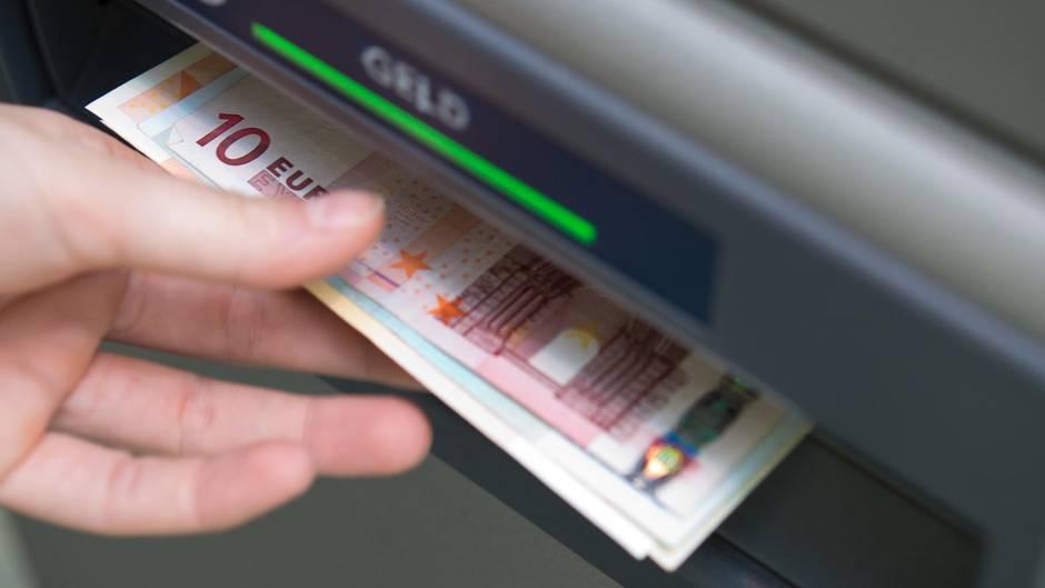 Eine linke Hand greift nach einem Euro-Scheinen, die aus dem Schacht eines Geldautomaten ragen