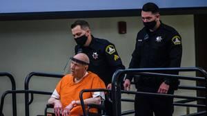 Ein Polizist fährt einen kahlköpfigen Mann in Rollstuhl und orangener US-Häftlingskleidung eine Rampe hinauf