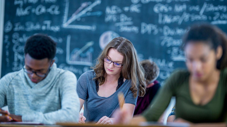 Schüler sitzen vor einer Tafel mit Formeln