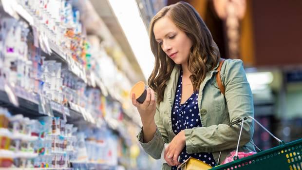 Eine Frau steht vor einem Regal mit Lebensmitteln in einem Supermarkt und schaut sich ein Produkt genauer an.