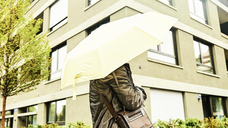 Jasmin mit Regenschirm vor einem Wohnblock