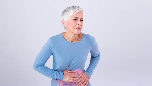 Eine Frau hält sich vor Schmerzen den Bauch