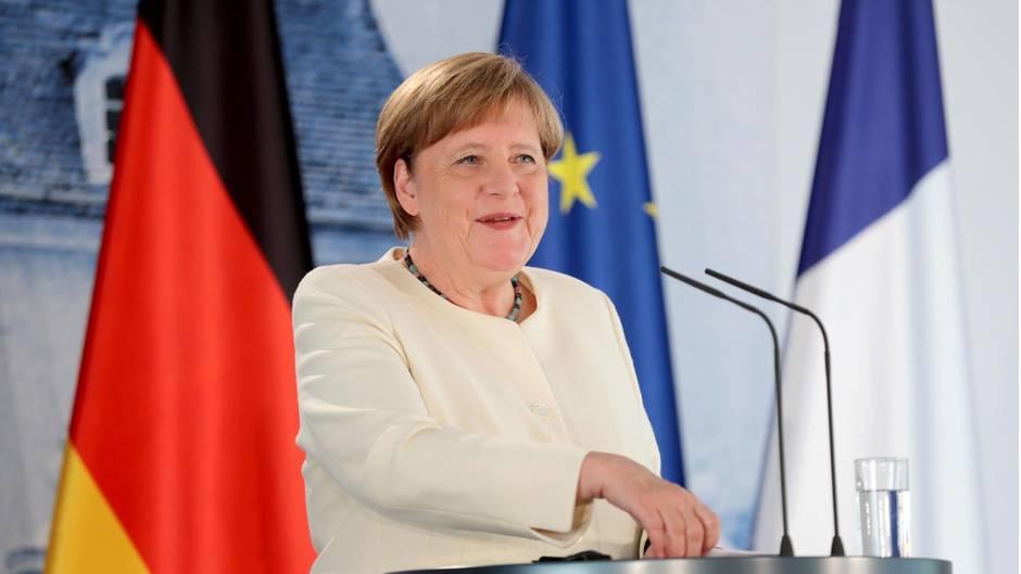 Angela Merkel steht an einem Rednerpult und lächelt