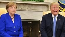 Donald Trump und Angela Merkel sitzen nebeneinander vor einem Kamin