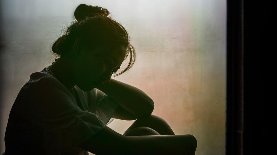 Junge Frau sitzt im Schatten vor einem Fenster und umschlingt ihre Beine mit ihren Armen