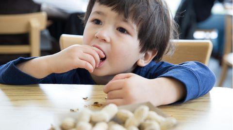 Ein Junge isst Erdnüsse