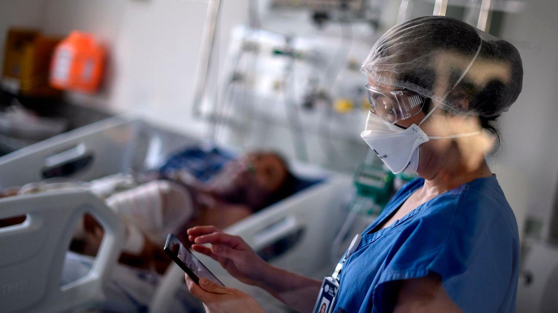 Krankenschwester mit Intensivpatient im Hintergrund