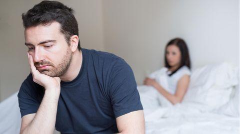 Mann sitzt traurig an der Bettkante