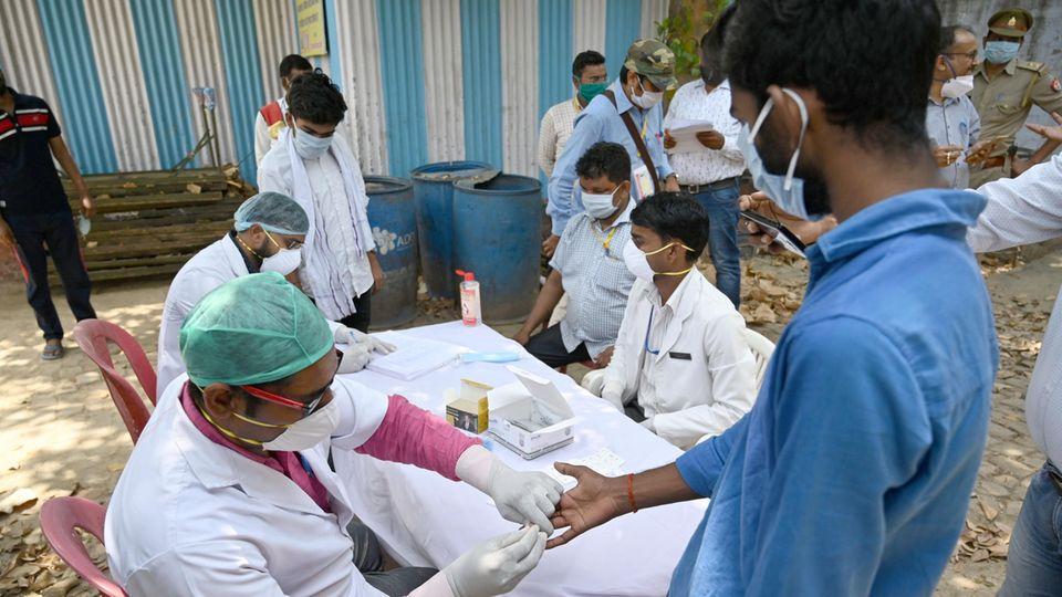 Mediziner in Indien machen Covid-19-Tests bei Studenten (Archivbild)