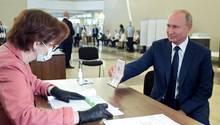 Wladimir Putin, Präsident von Russland, zeigt einer Mitarbeiterin der Wahlkommission seinen Pass in einem Wahllokal