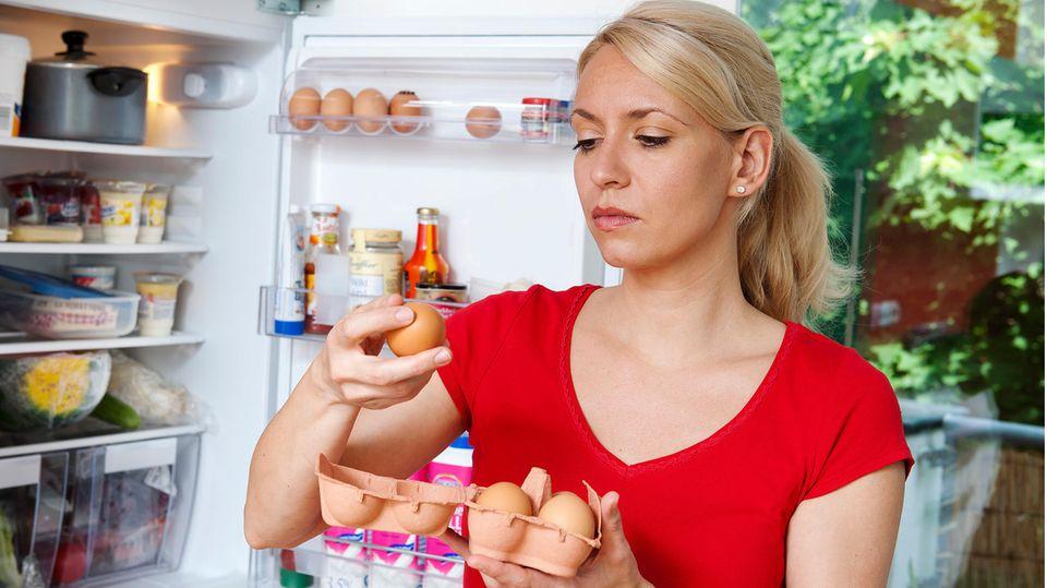 Frau prüft Eier auf ihre Haltbarkeit