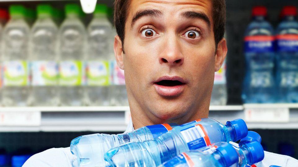 Mann hält Wasserflaschen im Arm