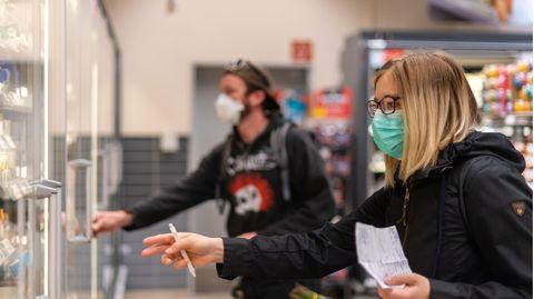 Kunden gehen in einem Supermarkt einkaufen und tragen dabei Mundschutz
