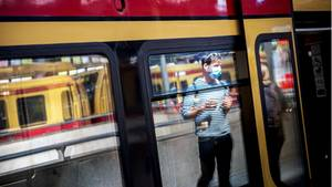 Ein Mann mit Mundschutz betritt am Ostbahnhof in Berlin eine S-Bahn