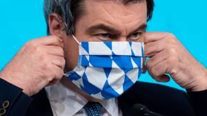 Bayerns Ministerpräsident Markus Söder richtet seine Atemmaske, die weiß-blau gemustert ist
