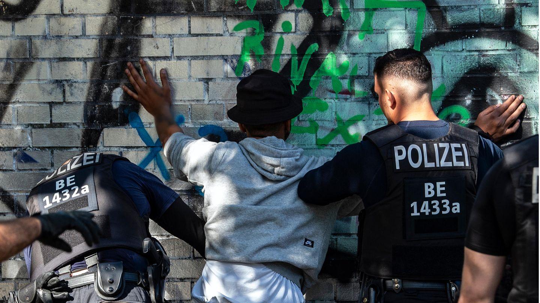 Polizistenkontrollieren in einem Berliner Park einen Mann mit dunkler Hautfarbe als mutmaßlichen Drogendealer